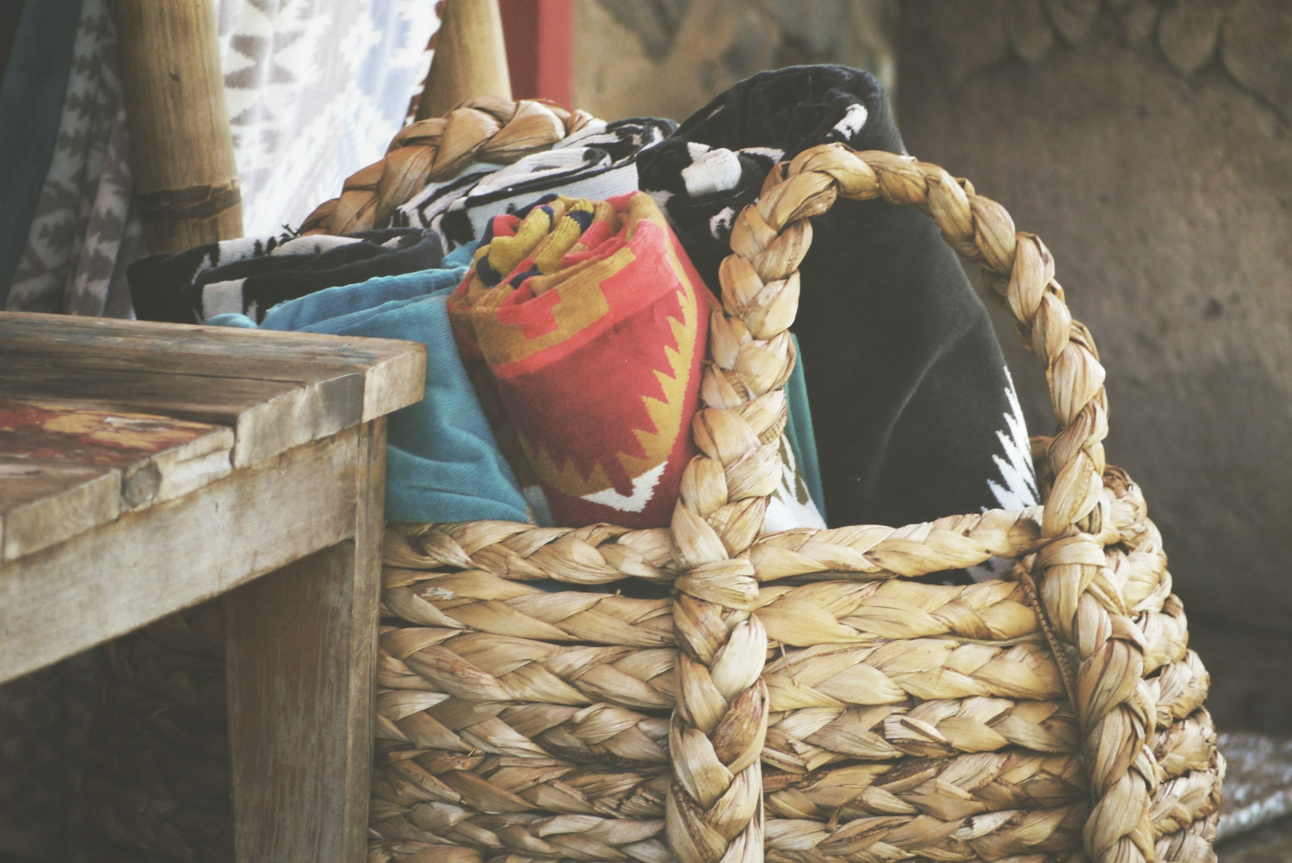 assorted rolled textiles on brown basket